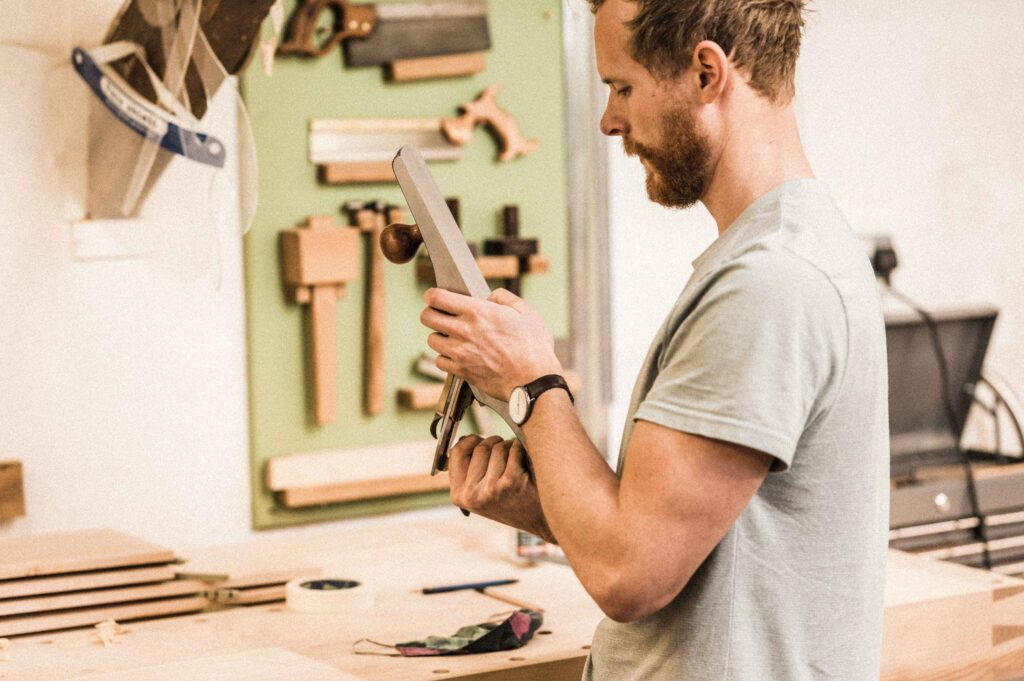 A STUDENT AT ROWDEN ON A FINE FURNITURE MAKING COURSE, WORKING ON FURNITURE COMPONENTS