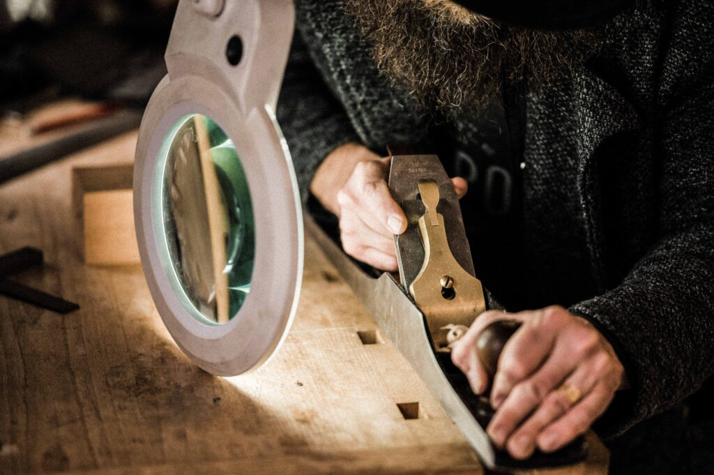 A STUDENT USING A HANDPLANE TO MAKE FURNITURE AS PART OF A FURNITURE MAKING COURSE AT ROWDEN ATELIER