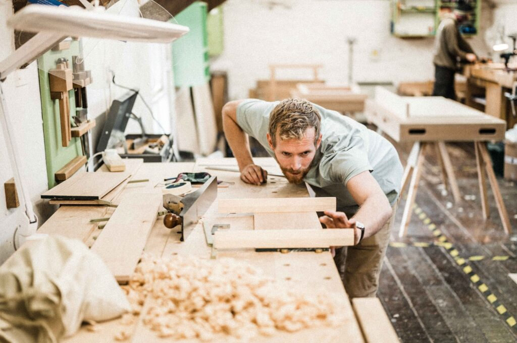 A STUDENT AT ROWDEN ATELIER ON A FINE WOODWORKING COURSE, CHECKING COMPONENTS WITH WINDING STICKS FOR TWIST.