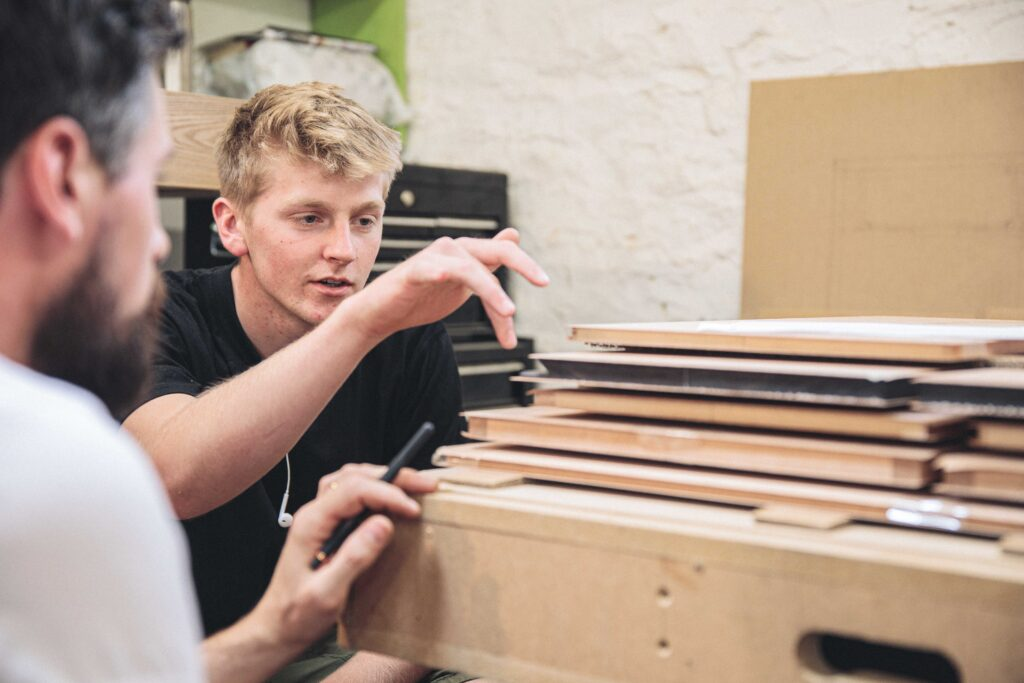 A STUDENT ON A ROWDEN ATELIER WOODWORKING COURSE DISCUSSING FURNITURE COMPONENTS