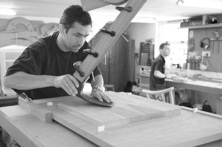 a student using an adze jig to sculpt a seat on a fine furniture making course at Rowden Atelier