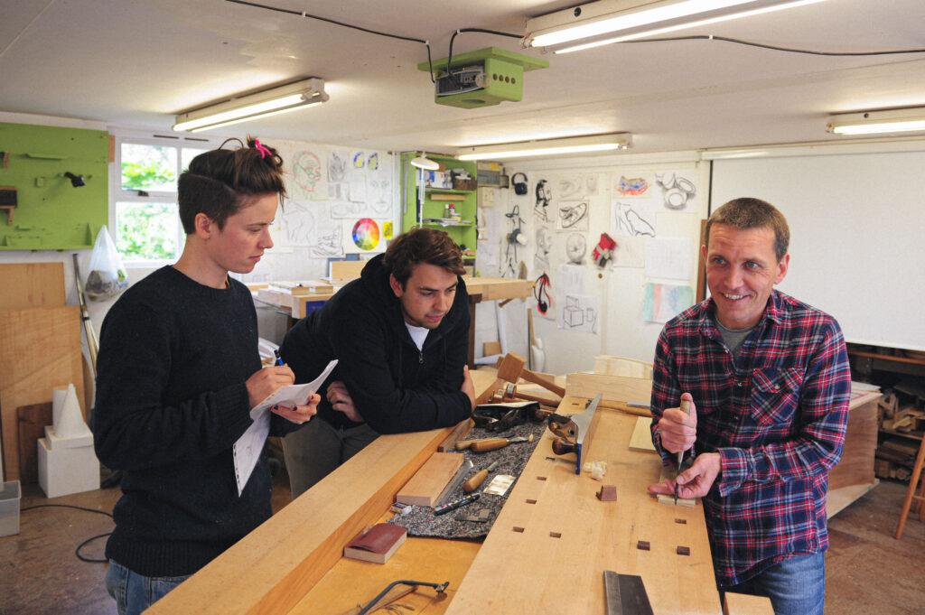 Rowden tutor Daren Millman demonstrating cutting dovetails to students in the workshop