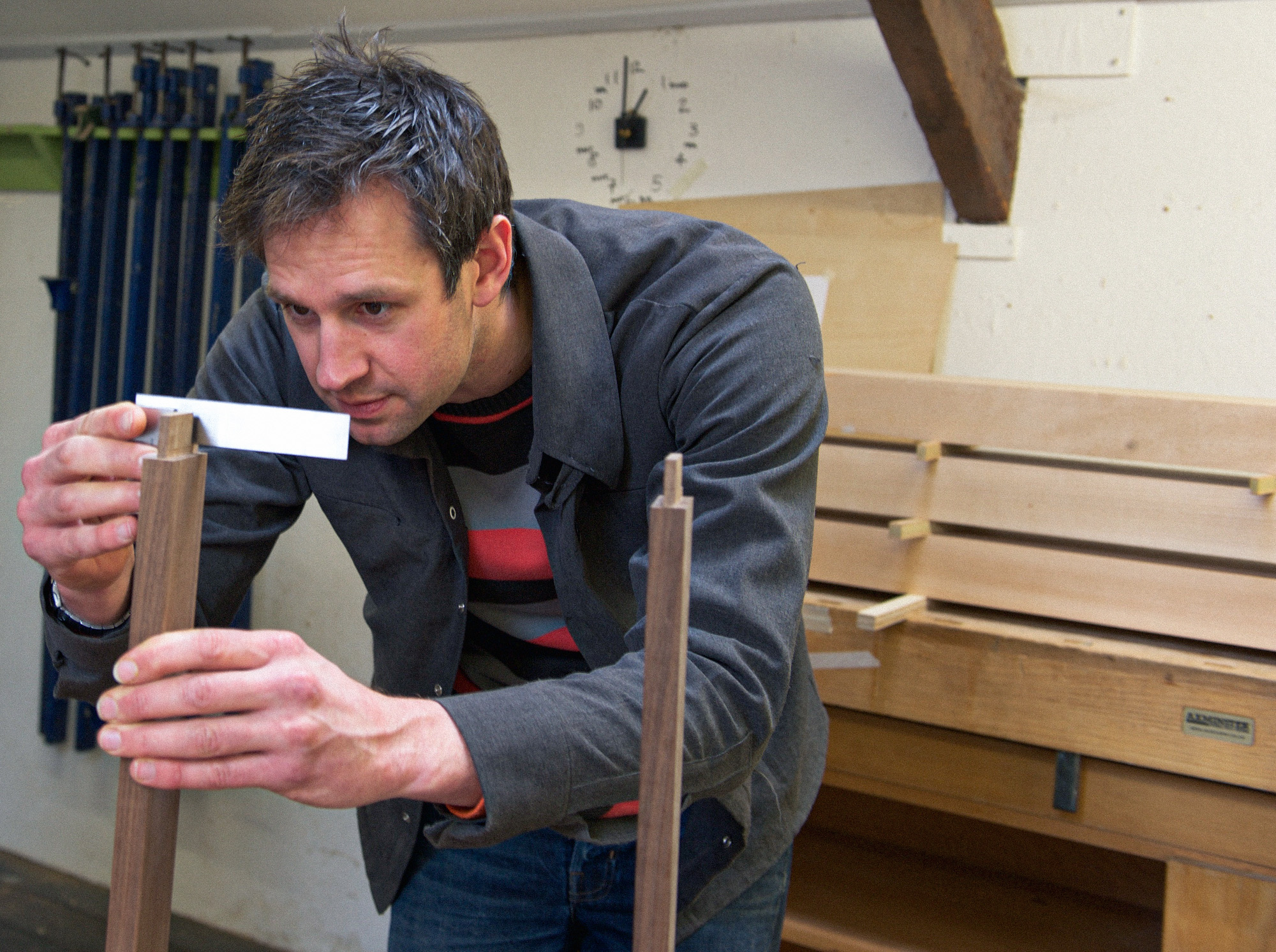 Rowden tutor Ed Wild checking a shoulder for square on a piece of furniture, made on a furniture making course at Rowden Atelier