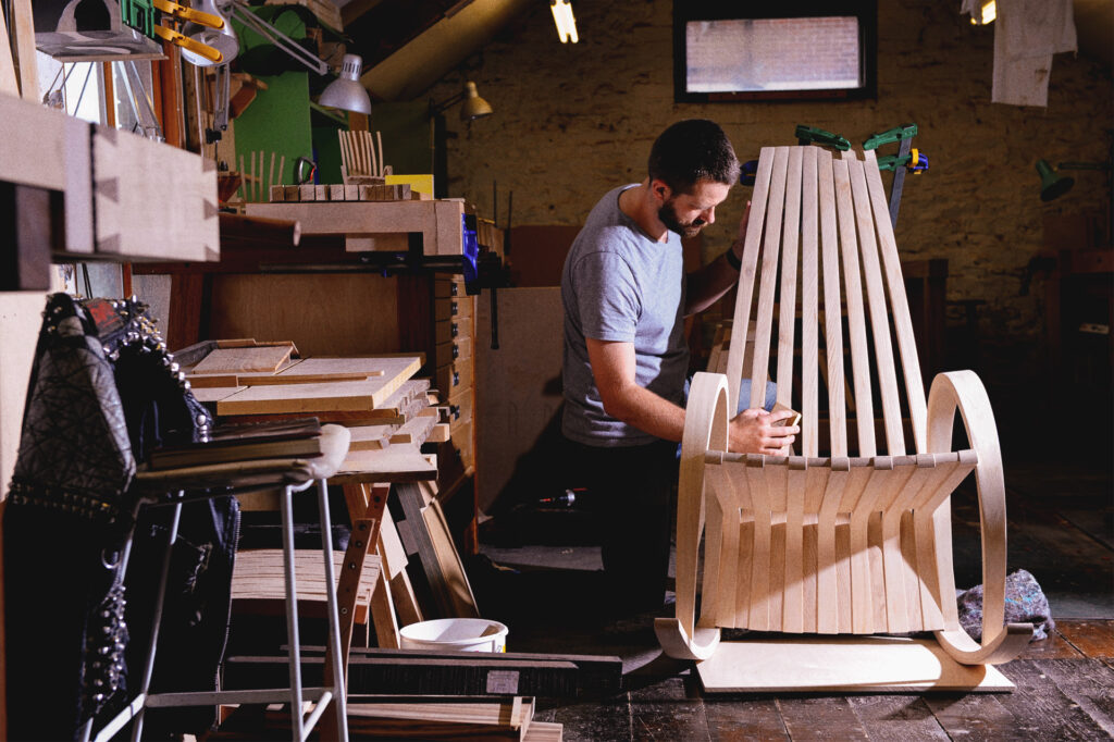 A student finishing a laminated rocking chair in ash at Rowden Atelier on a furniture making course