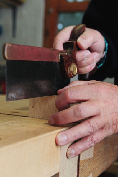 Rowden student, cutting into wood with a handsaw