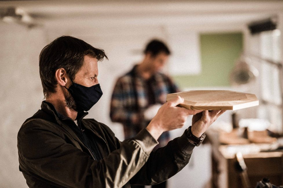 a tutor at Rowden checks accuracy of student work on a woodworking course at Rowden Atelier.