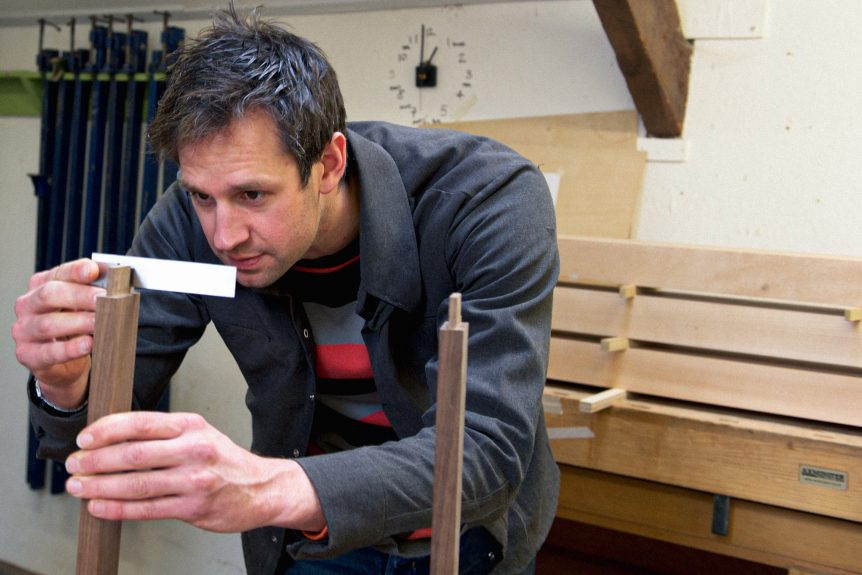 Rowden tutor Ed Wild checking a shoulder for square on a piece of furniture, made on a fine furniture design course at Rowden Atelier